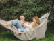 mother with children having fun in a hammock. Mom and kids in a hammock. The family spends time with the children in the garden.